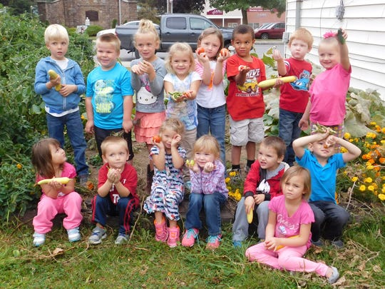 Children currently enrolled in the Blossburg 1 classroom of Bradford Tioga Head Start, Inc. show off some of the food grown in the garden they built as part of a collaboration with AmeriHealth Caritas.