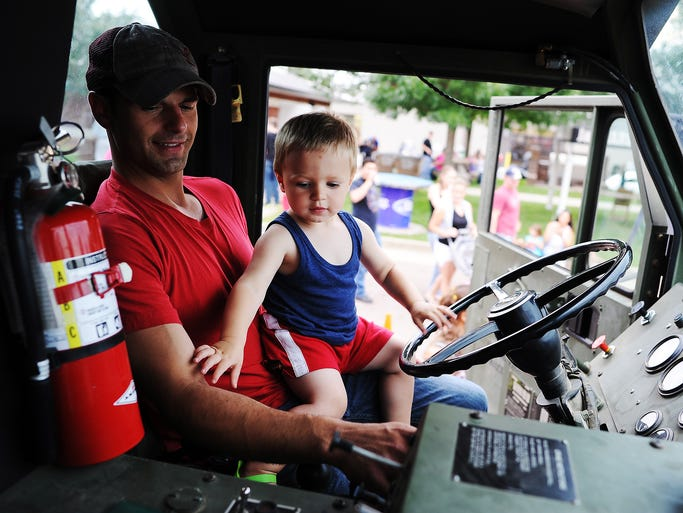 Jessie LaBahn and his 1-year-old son, Rayden LaBahn, both of Lyons, S.D., check out the inside of a military vehicle during the Hot Harley Nights Family Night on Thursday, July 10, 2014, at J&L Harley-Davidson in Sioux Falls, S.D. Family Night at J&L Harley-Davidson was added to Hot Harley Nights, which is in its 19th year, this year in an attempt to get whole families involved, explained Jimmy Entenman, with J&L Harley-Davidson.