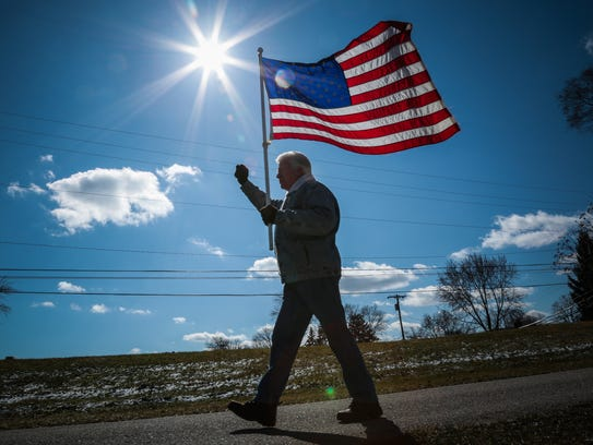 Roger H, 72, of Macomb Township, marches with others