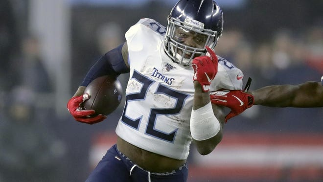 Tennessee Titans running back Derrick Henry runs from New England Patriots safety Duron Harmon in the first half of an NFL wild-card playoff football game Jan. 4, 2020, in Foxborough, Mass.