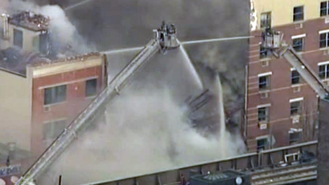 Firefighters battle a blaze at the site of an  explosion and building collapse in the East Harlem neighborhood of New York, March 12, 2014.