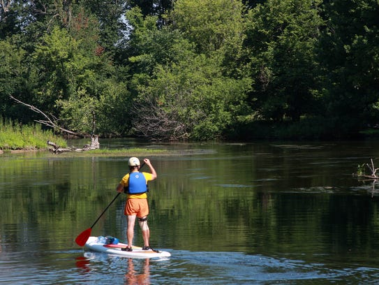A paddle-boater wades across the Kalamazoo River at