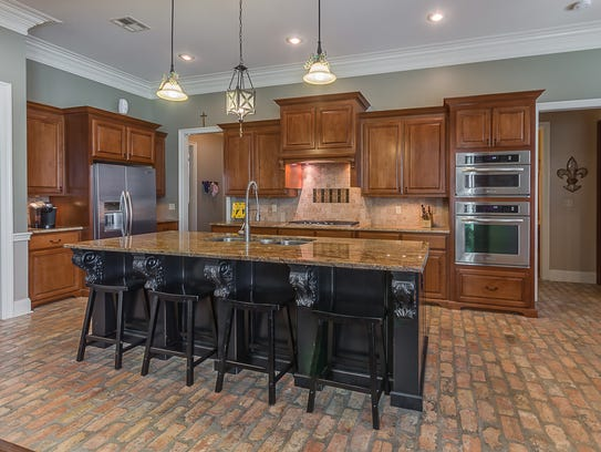 The kitchen includes top grade appliances and brick