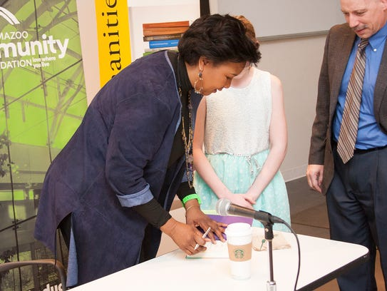 Astronaut Mae Jemison signs a book for a young fan.