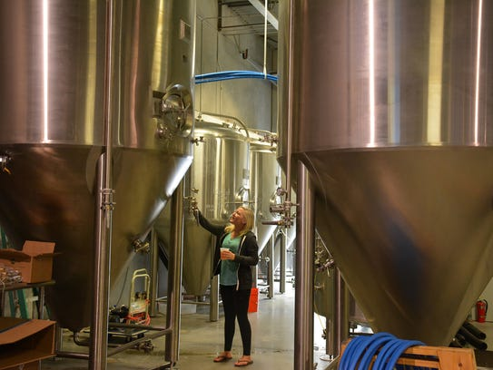 """""""Director of Fun"""" Kaitlin Griffin inspects the 1,860-gallon"""