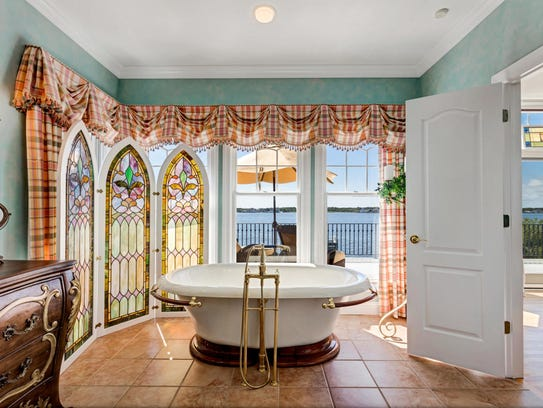 In the Master bathroom, there are decorative stained glass windows and tile flooring.