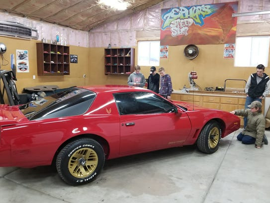 Friends of Obie Nef work on restoring a Pontiac Firebird.