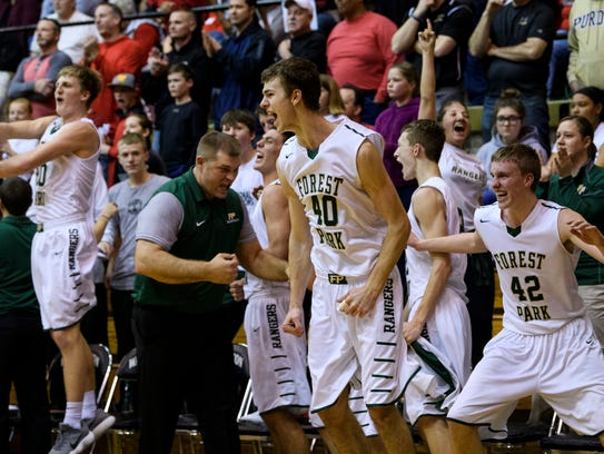 Forest Park's Collin Hochgesang (40) and the rest of the bench jump to their feet as their team defeats the Indianapolis Scecina Crusaders in the IHSAA Class 2A semistate matchup at the Hatchet House in Washington, Ind., Saturday, March 17, 2018. T