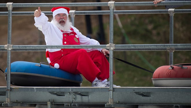 A Santa gives a thumbs up to the crowd as he and the other Santas ride to the top of the snow tubing park at Ober Gatlinburg on Friday, March 17, 2017. Santas from several different states came to Ober Gatlinburg to compete in a snow tubing race.