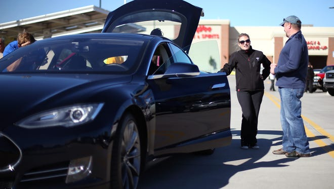 Brittany Thomas of Minneapolis speaks with Denny Ummel of Urbandale about one of the two Tesla electric cars she owns at the Hy-Vee on Douglas Avenue in Urbandale in this October 2014 photo.
