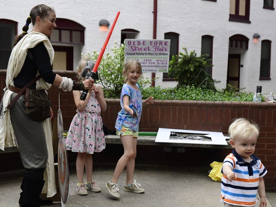 Holly Metzger-Brown, who is dressed as Rey from Star Wars, plays with children Tessa Scarpato, 6, Elana Scarpato, 8, and Jason Scarpato, 2, of Spring Garden Township as part of Give Local York's festivities in Cherry Court in York Friday, May 4, 2018.