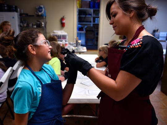 Sumer Russell helps Kodee Thibodeaux with putting on a rubber glove. About 15 kids attended a soapmaking class sponsored by the Stephens County Texas A&M AgriLife Extension Office in Breckenridge on Tuesday.