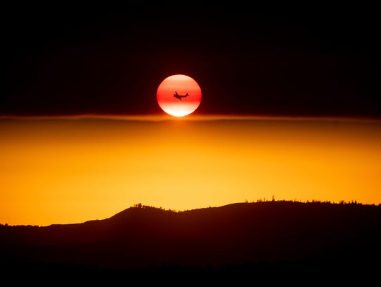 A plane battling the Ferguson Fire passes the setting sun in unincorporated Mariposa County, Calif., near Yosemite National Park on July 15, 2018.