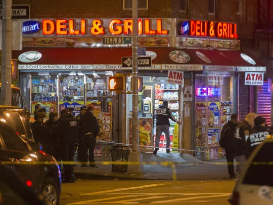 Investigators work in the area where two NYPD officers were shot.