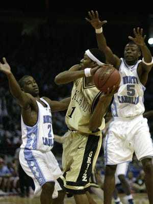 Oakland's Rawle Marshall is double-teamed by UNC's Raymond Felton, left, and Jackie Manuel in an NCAA tournament game March 18, 2005. The No. 16 seed Golden Grizzlies lost, 96-68, but they beat the spread.