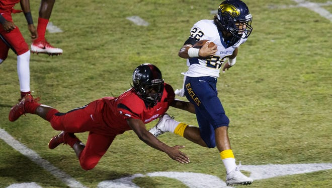 Naples High School's Chez Mellusi breaks free from South Fort Myers' Kam Crawford to score a touchdown during first quarter play Friday, Oct. 20, 2017 at South Fort Myers High School.