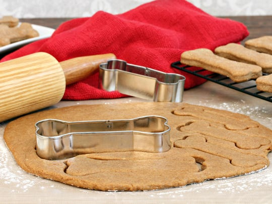 Dog biscuit dough is very similiar to cookie dough. You roll it with a rolling pin and use a bone-shaped cookie cutter.