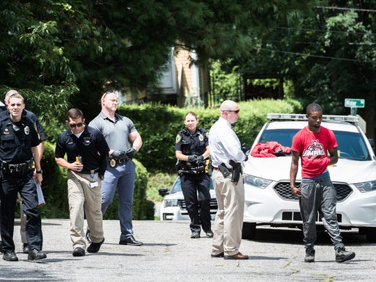 Asheville police officers question a man in the Erskine-Walton apartment complex after a report of a shooting in the around 10:30 am Tuesday morning, July 24, 2018. A-B Tech and Asheville high school and SILSA were on lockdown until about 11:30.