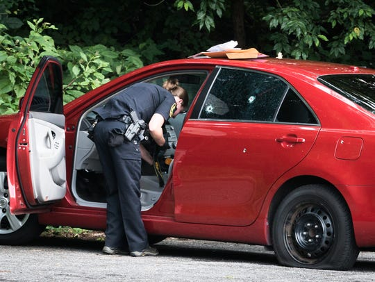 Asheville police officers search a vehicle with at