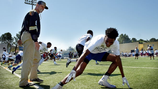 Michigan coach Jim Harbaugh looks on at a participate during the Pearl satellite camp.