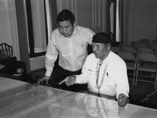 In this file photo, Herb Long (left), staff assistant to the Speaker of the Navajo Nation Council, looks on as Sam Begay, Navajo medicine man, points to the place where his grandfather signed the original Navajo-U.S. Treaty of 1868 (Naaltsoos Sani). The two were members of a recent delegation that went to the National Archives and Records Administration in Washington, D.C., to discuss bringing the treaty to Northern Arizona University in Flagstaff, Arizona, for a one-year educational exhibition in 1998.