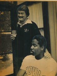 A smiling Hayden Fry and serious Reggie Roby stand