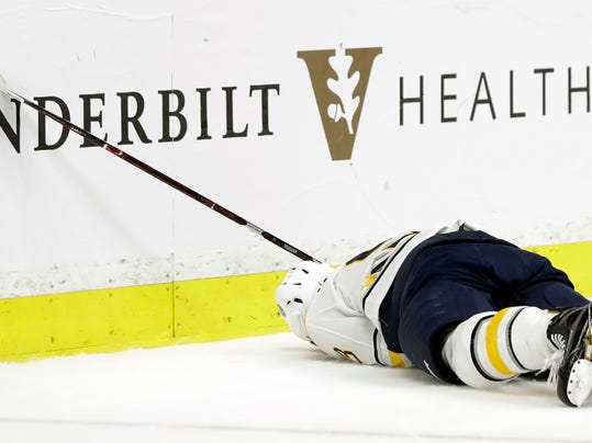 Buffalo Sabres defenseman Victor Antipin (93), of Kazakhstan, lies on the ice after being checked into the boards by Nashville Predators left wing Scott Hartnell in the second period of an NHL hockey game Saturday, March 31, 2018, in Nashville, Tenn. Antipin was taken off the ice on a stretcher. Hartnell was given a game misconduct penalty for boarding. (AP Photo/Mark Humphrey)