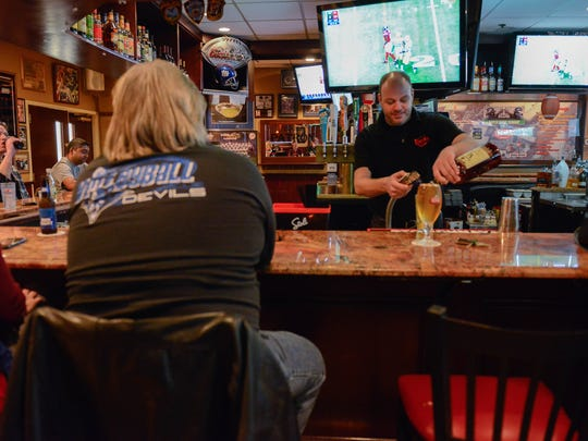 Bartender Jamil Rashid serves patrons at Redd's on Sunday. He said that normally the establishment is packed.