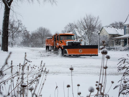 A city plow truck travels along Court Street in Port