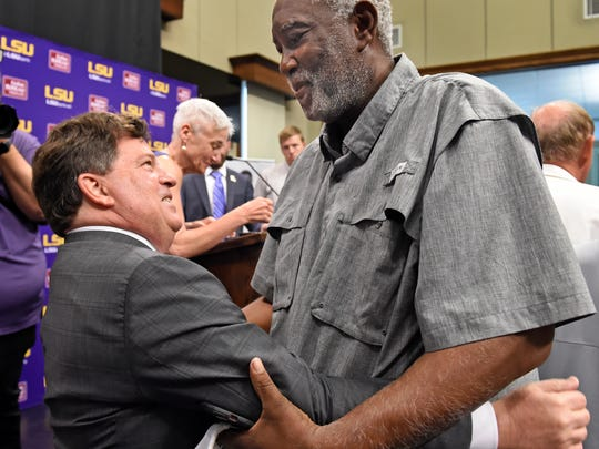 Former LSU basketball player Collis Temple Jr., right, greets Scott Woodward, left, after Woodward was introduced as the new Director of Athletics at LSU, Tuesday April 23, 2019, in Baton Rouge, La. Woodward, who graduated from LSU in 1985, was the Vice-Chancellor of External Affairs at his alma mater under former Chancellor Mark Emmert from 2000-2004. Woodward spent time at Washington and Texas A&M before accepting the job at LSU as a replacement for Joe Alleva. (Bill Feig/The Advocate via AP)