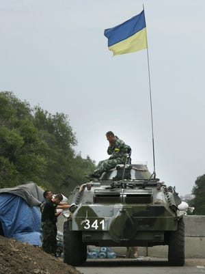 Ukrainian forces guard  a checkpoint in the town of Mariupol, eastern Ukraine, Aug. 28, 2014.