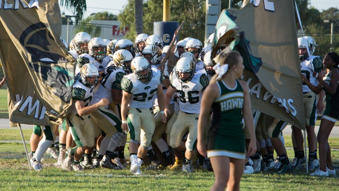 Opening their first game of the year Viera High's football team bursts through the team banner.
