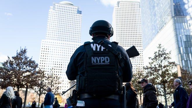 A New York Police Department officer stands guard outside of the 9/11 Memorial  following a series of terrorist attacks in the French capital on November 14, 2015 in New York City. Security in New York City has increased following the  a coordinated assault on Paris which ISIS claimed responsibility for that left more than 130 people killed and hundreds injured.