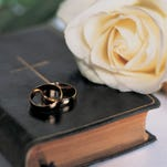Two Gold Wedding Bands on a Bible With a Rose