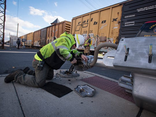 Norfolk Southern employee Tony Tribioli disconnects the gatemast at the intersection of N 8th Street and Scull in Lebanon. The railroad guard was hit by a driver who then drove away.
