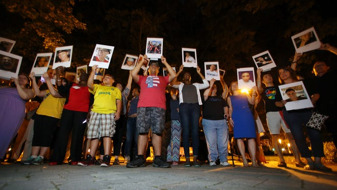 Community members hold photos of all 49 victims of the Orlando massacre on the Morristown Green during the Church of the Redeemer's their 'Interfaith Vigil for Orlando: Solidarity and Love.'  June 15, 2016, Morristown, NJ