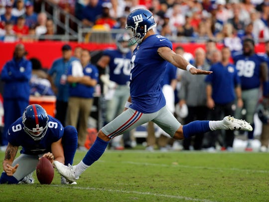 New York Giants kicker Aldrick Rosas (2) kicks a field goal as punter Brad Wing (9) holds the ball during the first half at Raymond James Stadium.