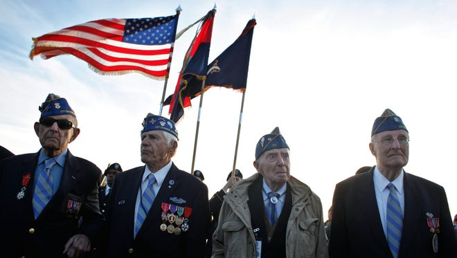 From left, World War II veterans of the U.S. 29th Infantry Division, Hal Baumgarten, 90, from Pennsylvania, Steve Melnikoff, 94, from Maryland, Don McCarthy, 90 from Rhode Island, and Morley Piper, 90, from Massachusetts, attend a D-Day commemoration, on Omaha Beach, western France , Friday June 6, 2014. Veterans and Normandy residents are paying tribute to the thousands who gave their lives in the D-Day invasion of Nazi-occupied France 70 years ago. World leaders and dignitaries including President Barack Obama and Queen Elizabeth II will gather to honor the more than 150,000 American, British, Canadian and other Allied D-Day troops who risked and gave their lives to defeat Adolf Hitler's Third Reich.
