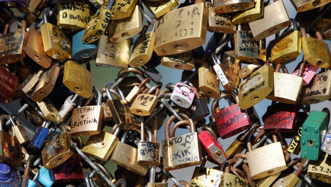 Love locks are fixed on the Pont des Arts Wednesday, April 9, 2014 in Paris.