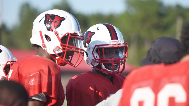 Petal wide receivers Natorian, left, and Nataurean Watts speak to a coach during practice at Petal High School on Wednesday.