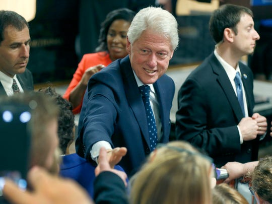 Bill Clinton shakes hands with supporters of his wife