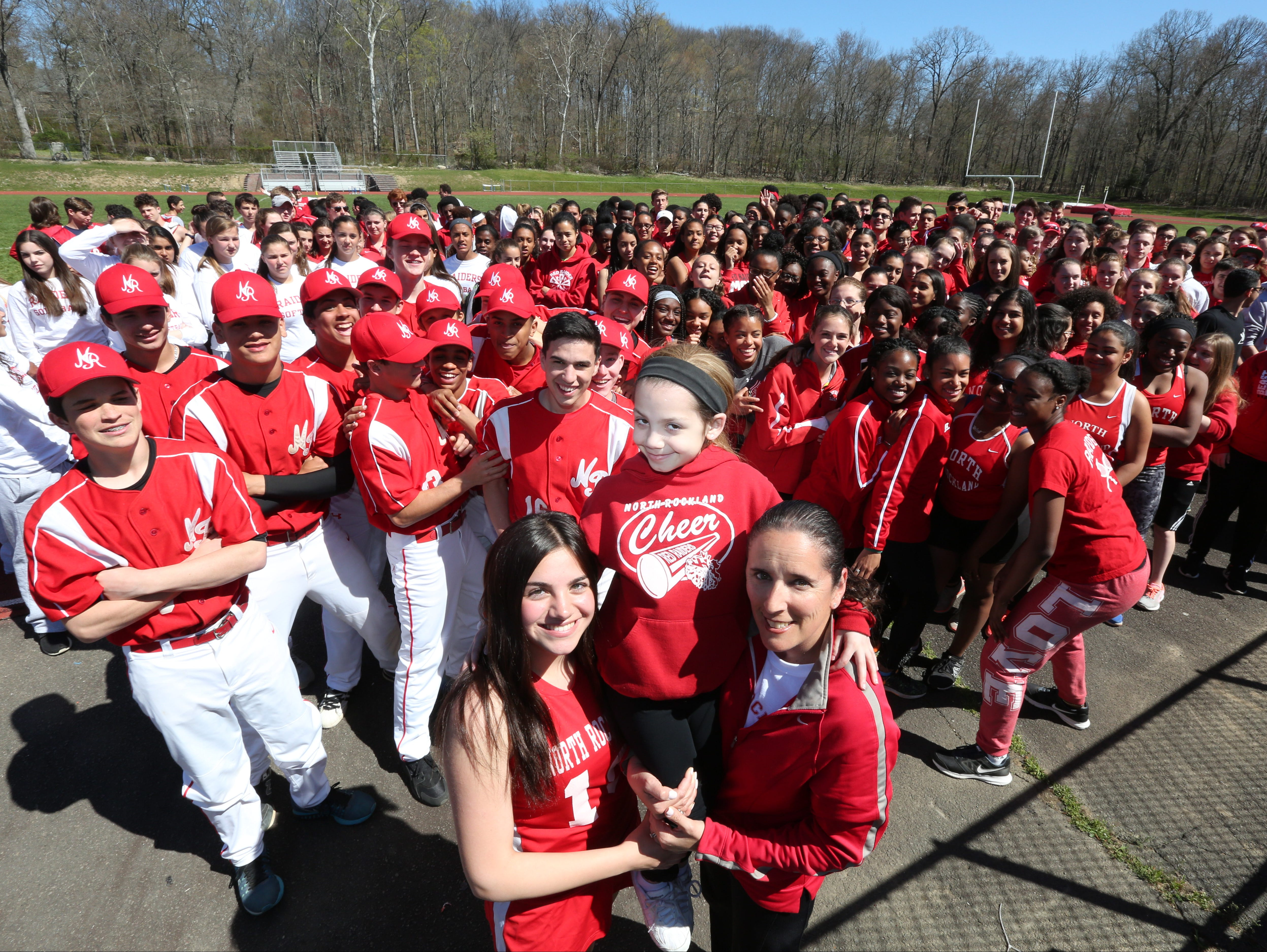 """Athletes gather behind Stony Point Elementary third-grader Gabby DiCarlo, who is being held up by her sister, Isabella DiCarlo and Jennifer LaBier, Stony Point Elementary teacher and high school tennis coach, at North Rockland High School April 20, 2016. They got together to spread the word about the second annual """"Sports Day"""" at the high school on April 30. So far they have raised $14,000 for cancer and cystic fibrosis."""