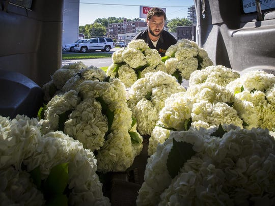 """Tim Boesen of Boesen the Florist loads an order of hydrangeas for delivery Thursday, July 30, 2015, from their branch on Ingersoll Avenue in Des Moines. Iowa's average gas prices are about 70 cents below the same price a year ago. That's a big boost to businesses like Boesen the Florist, which spends a lot getting flowers to the shops and delivered to customers. Owner Tom Boesen said the family-owned business decided against raising prices a year ago when a gallon of gas went over $3.50 a gallon, so he's happy to see them fall. """"That's money in my pocket,"""" he said."""