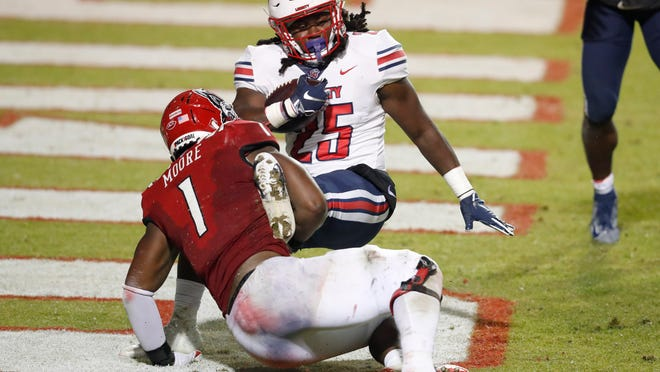 NC State linebacker Isaiah Moore (1) tackles Liberty running back Peytton Pickett in the end zone for a safety in their game last month. The Wolfpack won 15-14.