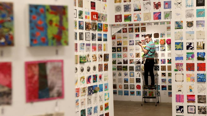 "Nilson Carroll, an intern at Rochester Contemporary Art Center, fills an open space as the ""6x6x2015"" display goes up."