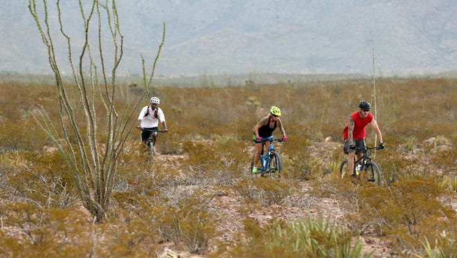 A trio of cyclists ride one of the trails in the Lost Dog Trailhead area of West El Paso on July 28. The site is at the center of a controversial plan by the city of El Paso to redevelop the land as a mixed-use commercial and residential space.