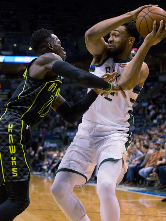 Milwaukee Bucks forward Jabari Parker, right, is defended by Atlanta Hawks guard Dennis Schroder, left, during the first half of an NBA basketball game Tuesday, Feb. 13, 2018, in Milwaukee. (AP Photo/Darren Hauck)