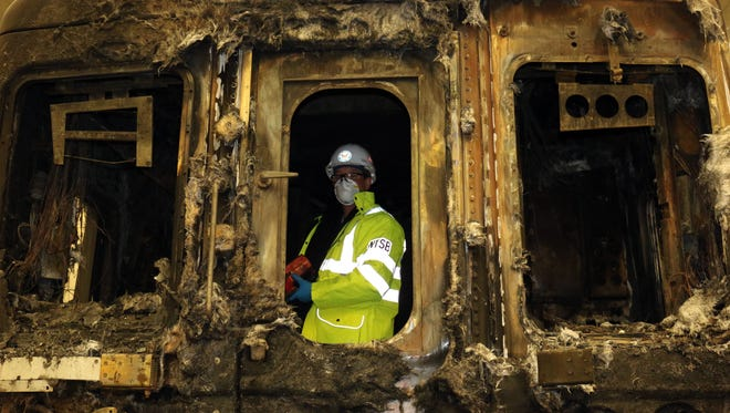 An NTSB investigator examines inside burned train from the Feb. 3, 2014,   Metro-North accident. It has been removed from the Valhalla, N.Y., crash site and is at a maintenance facility.