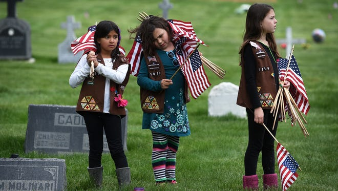 From left, Girl Scout Troop 1019 members Priyasha Landry, Nora Downs and River Grayden pause while placing flags on the gravestones of veterans at Our Mother of Sorrows Catholic Cemetery in Reno on May 23, 2015.