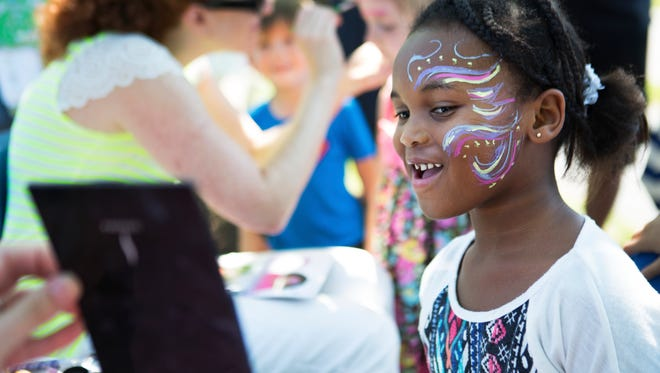 Aryana Powell, 6, of Rochester checks out her face paint in a mirror at the Parenting Village's Summer Bash in Rothfuss park in Penfield on Sunday, July 26, 2015.